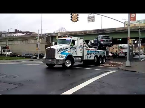 Heavy Wrecker Tows Away A Tandem Vehicle Transporting Truck Involved In A MVA In The Bronx