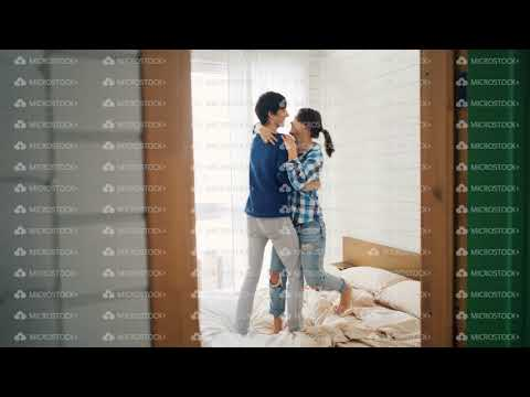 Cheerful young lovers are dancing on bed at home having fun in bedroom and laughing carelessly