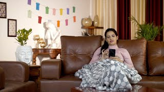 Young beautiful woman using her mobile while sitting alone at home during the winter season