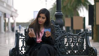 Pretty Indian office girl doing card payment via her smartphone - technology concept