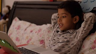 Cute and Excited Indian child watching cartoons on laptop before sleeping