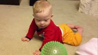 Baby with Down syndrome playing with parents and laughing