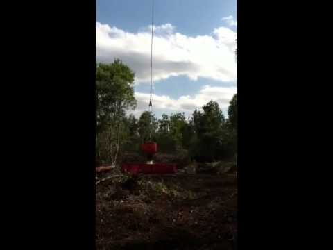 Helicopter pilot drops water for forestry firefighters in n