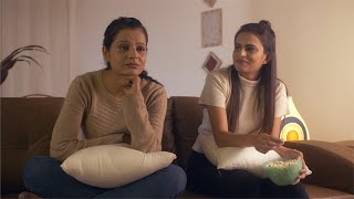 Beautiful Indian girl making fun of her sad friend / sister at home