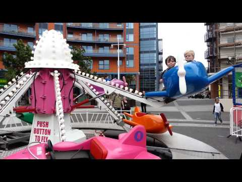 Kids riding theme park aeroplane by themselves