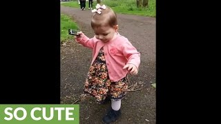 One-year-old girl preciously plays the harmonica