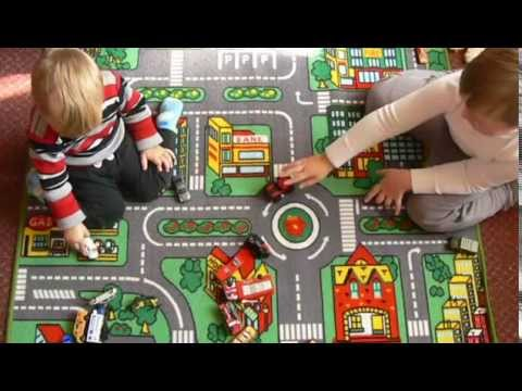 Kids playing with toy cars on carpet with roads and city buildings