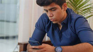 Smart Indian boy typing a message in his mobile phone while waiting for his friend in a restaurant