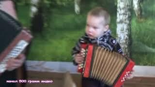 Дед и двух летний внук весело играют на гармошке