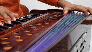 Close up shot of a man playing Indian traditional musical instrument harmonium