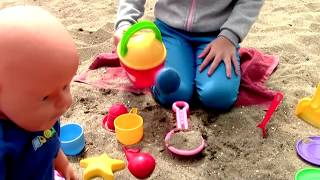 Kid and Dolls Play with Toys from sand on the Beach