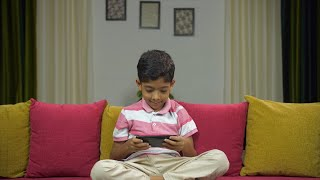 Cute Indian kid playing mobile games while sitting on a couch - lifestyle kids