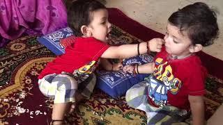 Twins baby feeding each other