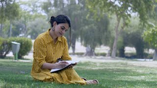 Young attractive girl writing into her notebook while sitting on the green grass in a park - leisure concept