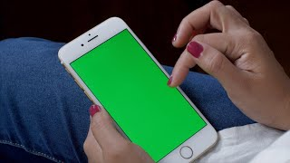 Female using smartphone mobile with green screen - scrolling and tapping the touchscreen