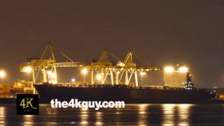 4K UHD - Huge cargo ship at night with cranes lifting containers in port