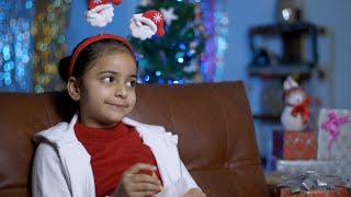 Pretty Indian girl having potato fries while sitting alone in a decorated Christmas room