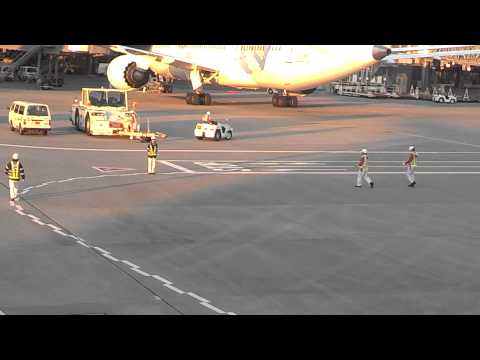 Ground crew at Tokyo HND airport bow to AA 777