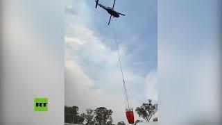Un helicóptero saca agua de una piscina para apagar un incendio en Australia