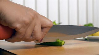 Woman using a knife to cut spicy green chili on cutting board