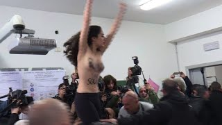 Former Italian PM Berlusconi confronted by topless activist