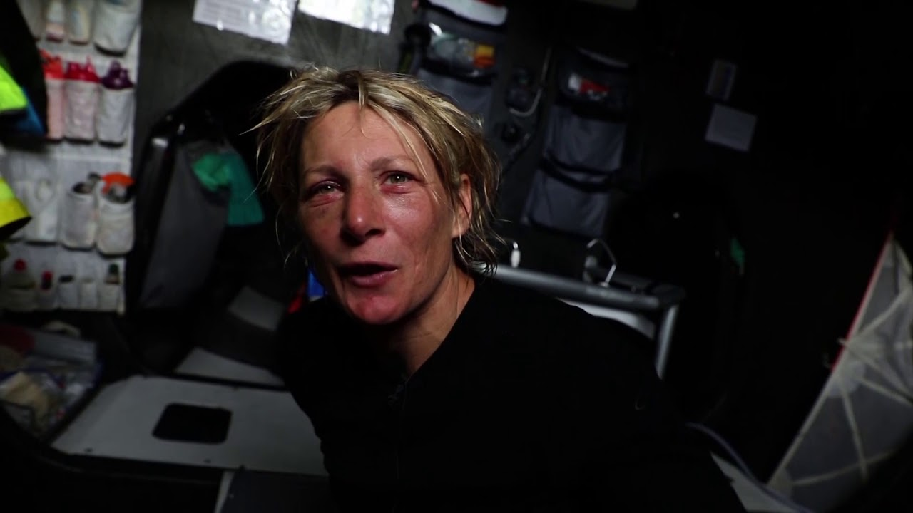 "Brunel sails downwind. Crew in the cockpit, at the mast. Abby comes below, inspects the steering hardware in the stern. Kyle, below: Talks about receiving the news about the loss of John Fisher. Absolutely devastating for everyone on board. Naturally morale is down. Thoughts are first and foremost with those guys; racing is secondary. Nina talks about it: Makes everything out here very real; all the risks involved. On deck, crew working in the cockpit. Below, Someone (Thomas?) grimacing as he works on something involving his hand, and blood. Abby, below: Movement of the boat is heinous. So just trying to take care of yourself, bit of an eye infection (she indicates her swollen, red eyelids) gets lower down on the priority list. Looking forward to flat water. Nina, Kyle eating. Kyle talks about how hazardous it is: Yann (OBR) fell and hurt his back. Nina fell and hit her head. Abby took a runner block to the head. ""These boats are dangerous and this is a dangerous part of the world."" Abby: Nina was in the head area, and we nosedived, and the boat comes to a sudden stop, and I watched her go from the head to the forward bulkhead and landed on her head. Looked awful, and I thought there was going to be serious injury. Nina: I tried to move my fingers and toes... Went straight into her bunk. Thnks she was really lucky. It's really dangerous for smaller people; ther'es nothing to hold onto. Dusk shots in the cockpit as they sail fast with the moon ahead of them."