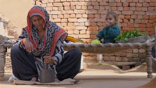 A mother in a village home is pounding bajra with mortar and pestle while her baby is sitting on the cot