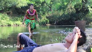 Primitive life: skills catch big fish by hand in the river and cooking fish
