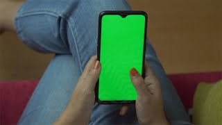Woman hands typing and sending messages from her green screen smartphone
