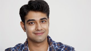 Handsome looking young Indian man with a white backdrop/ background
