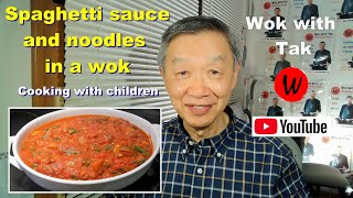 Cooking spaghetti sauce and noodles in a wok.  Cooking with children.