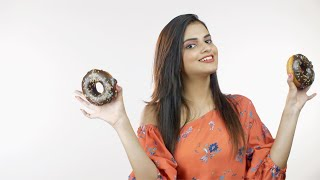 Young pretty girl happily playing with chocolate donuts against white background