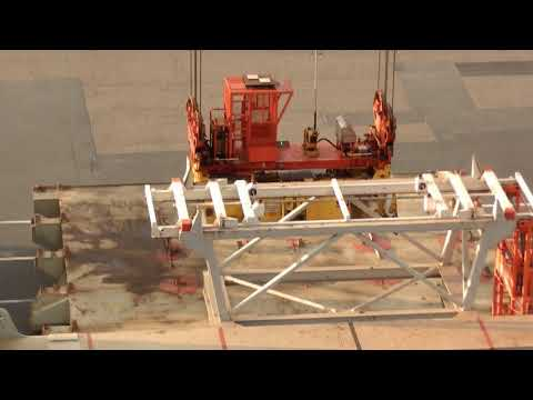 Lifting a gigantic hatch cover onto its place onboard a container ship
