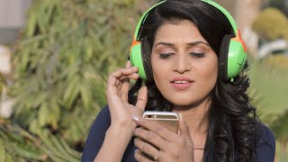 Young girl sitting outdoor listening to music on headphones and singling along