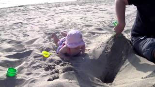 Sadie watching Tim dig in sand Thumbnail