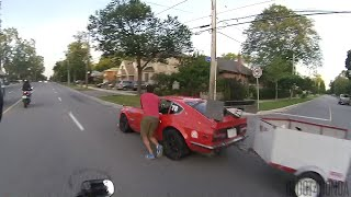 motorcycle pulls over to help car driver