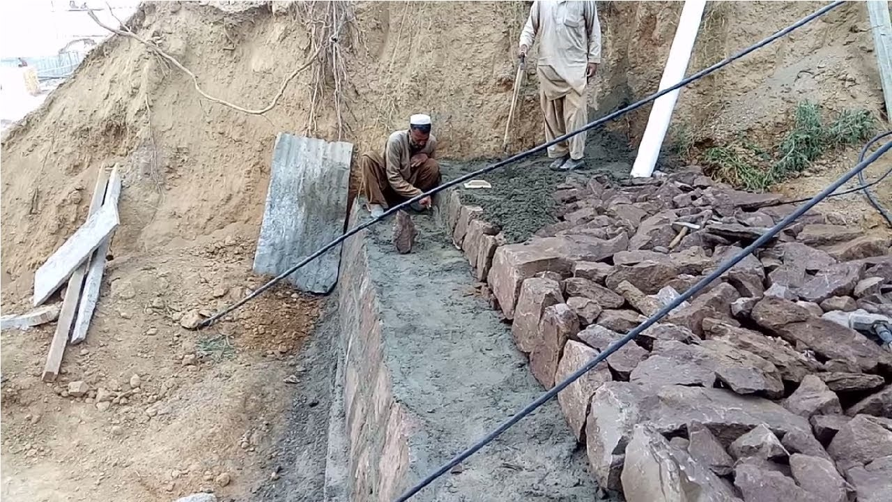 Stone masonry retaining wall construction