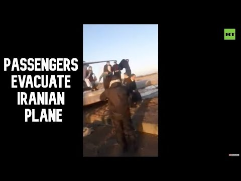 Passengers evacuate Iranian plane after it skids off runway, stops in middle of road