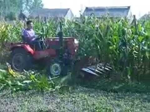 Four wheel farm tractor with reaper harvester cutting table harvest corn