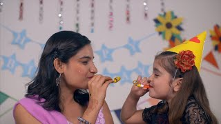 Pretty Indian young mother and her daughter blowing blow out whistle at each other at a birthday party