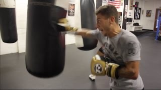 LUCIEN REID POUNDS THE HEAVY BAG IN CAMP WITH TRAINER PETER SIMS / iFL TV