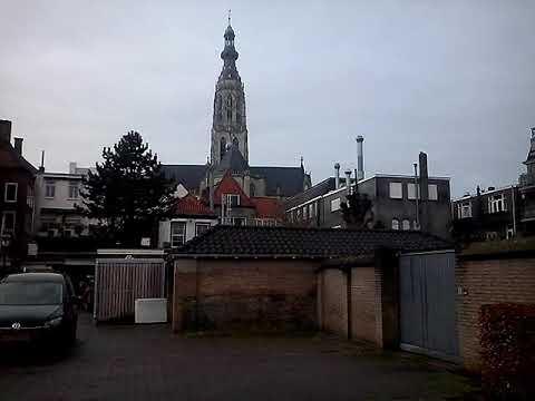 Grote kerk in Breda slaat twaalf uur, klokken van de Antonius klinken nog na.