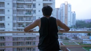 Muscular Indian young man exercising and stretching in the balcony