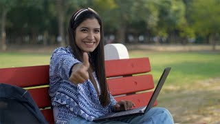 Cute Indian student smiling and showing a thumbs up while working on her laptop