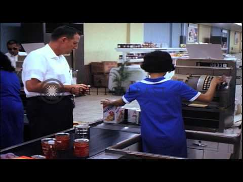 USAF personnel buy food items and a Vietnamese woman works oata cash register in ...HD Stock Footage