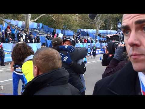 Hugh Jackman embraces Gus Worland at the end of the 2014 New York City Marathon