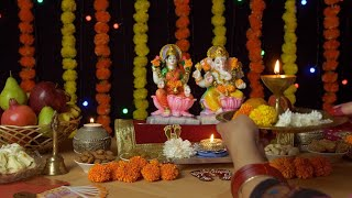 Indian female praying in front of Ganesh Ji and Laxmi Ji with a Puja thali on Diwali
