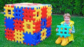 एली खिलौना ब्लॉकों के साथ भवन निर्माण का नाटक करता है