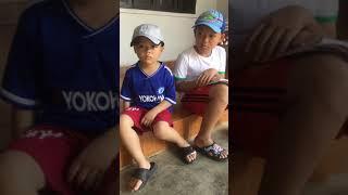 2 bé trai ngồi đọc truyện tranh Doremon