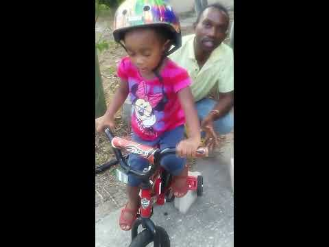 Teaching 3 year old toddler how to pedal a bicycle.
